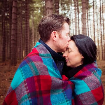 Engagement shoot Photography at Newmillerdam Wakefield, Couple embrace each other while wrapped up in winter blanket