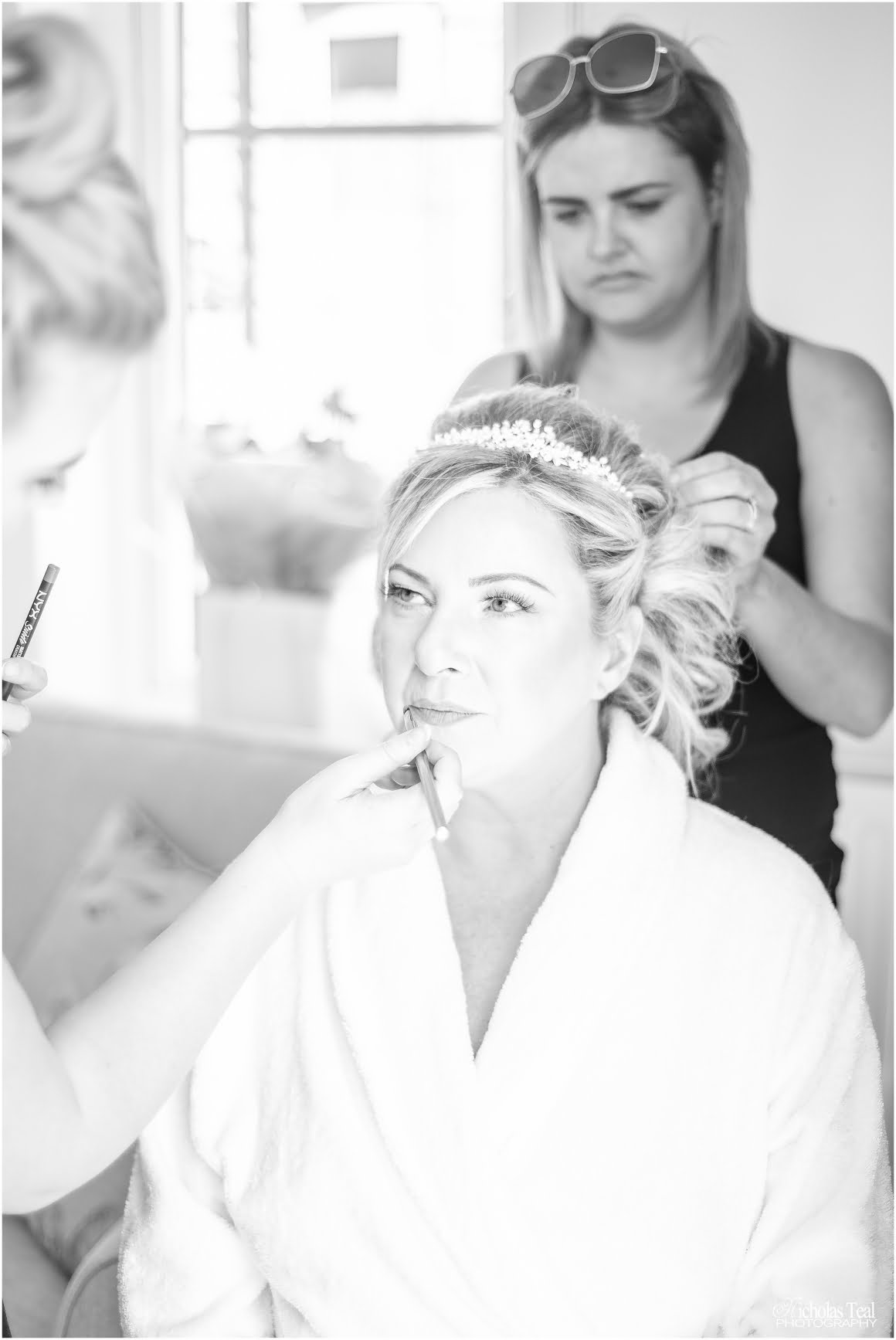 Black and white shot of bride and makeup artist putting lipstick on