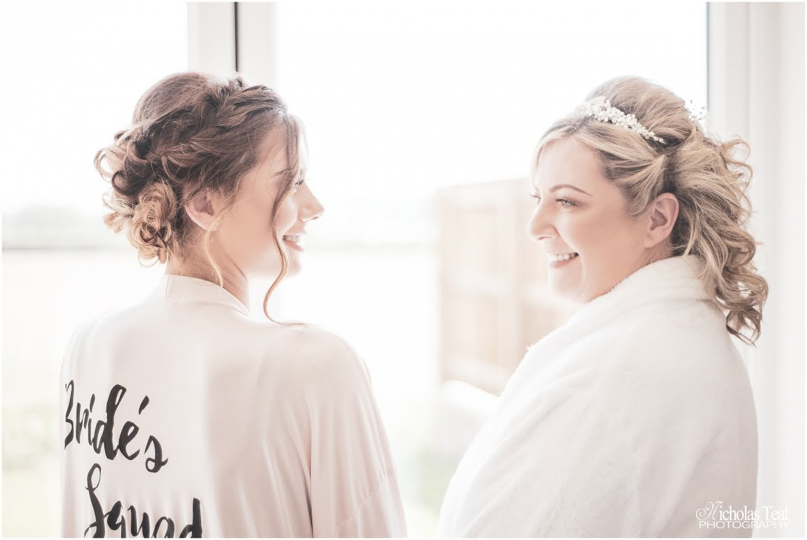 bride and bridesmaid smilling at each other pre wedding prep pichure