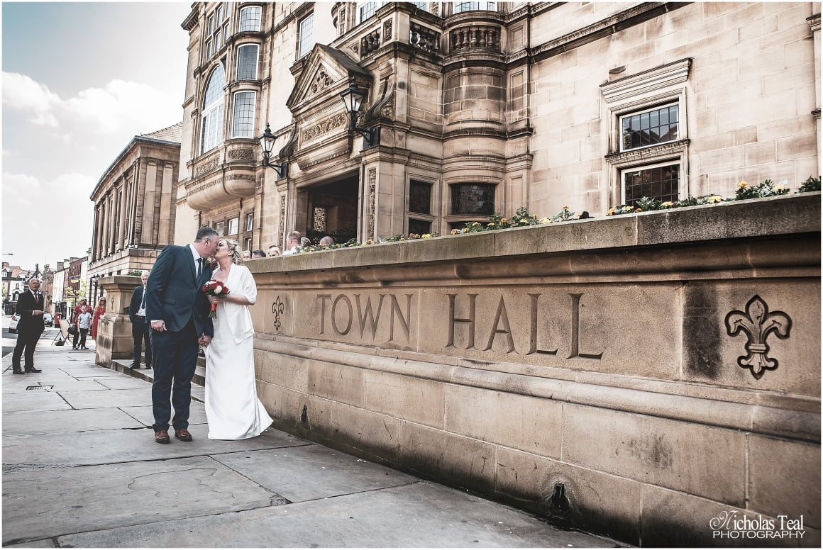 classic shot of bride and groom kissing outside the town hall stood next to town hall sign