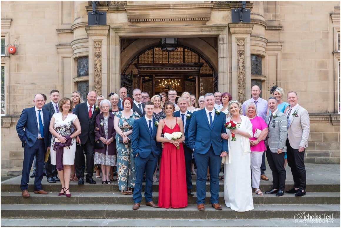the wedding party stood on the town hall steps