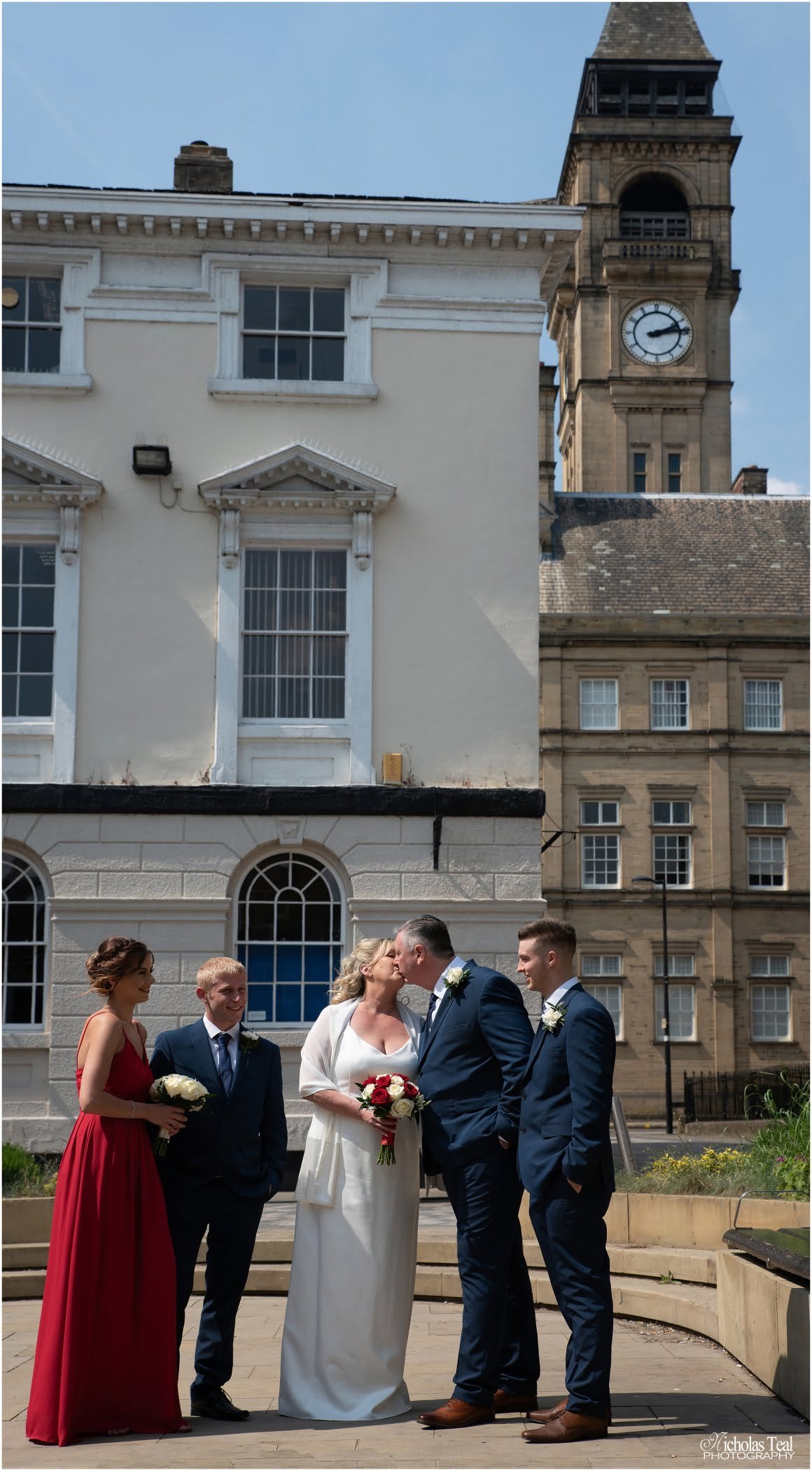 shot of bride and groom kissing with the town hall clock tower in the back ground