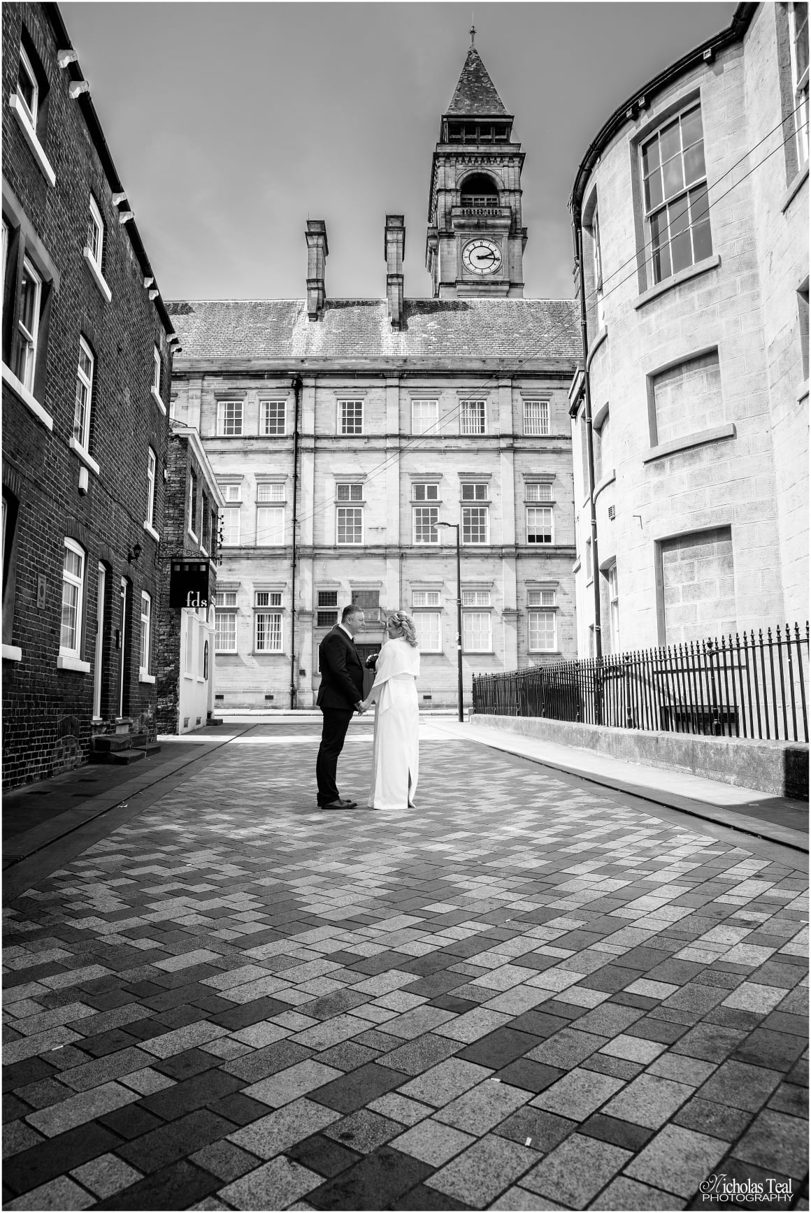 black and white picture of birde and groom in the street behind the old museum with the town hall clock tower in the back ground