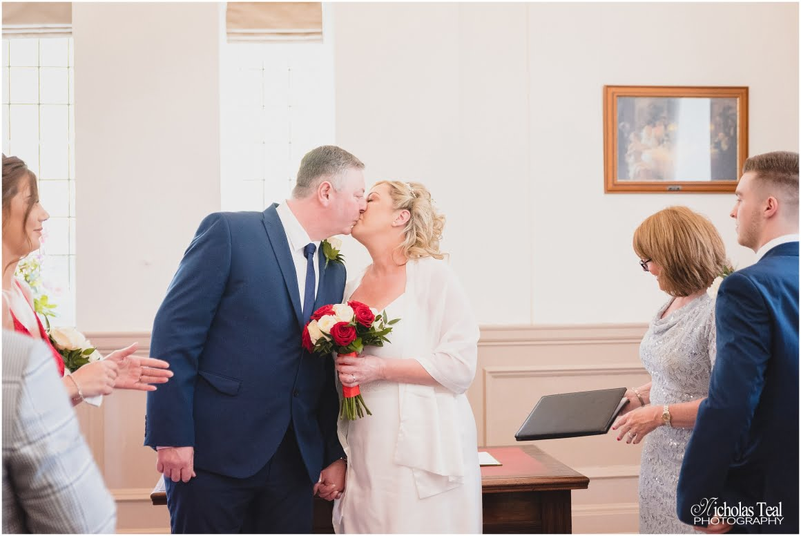 bride and groom kissing at wedding service