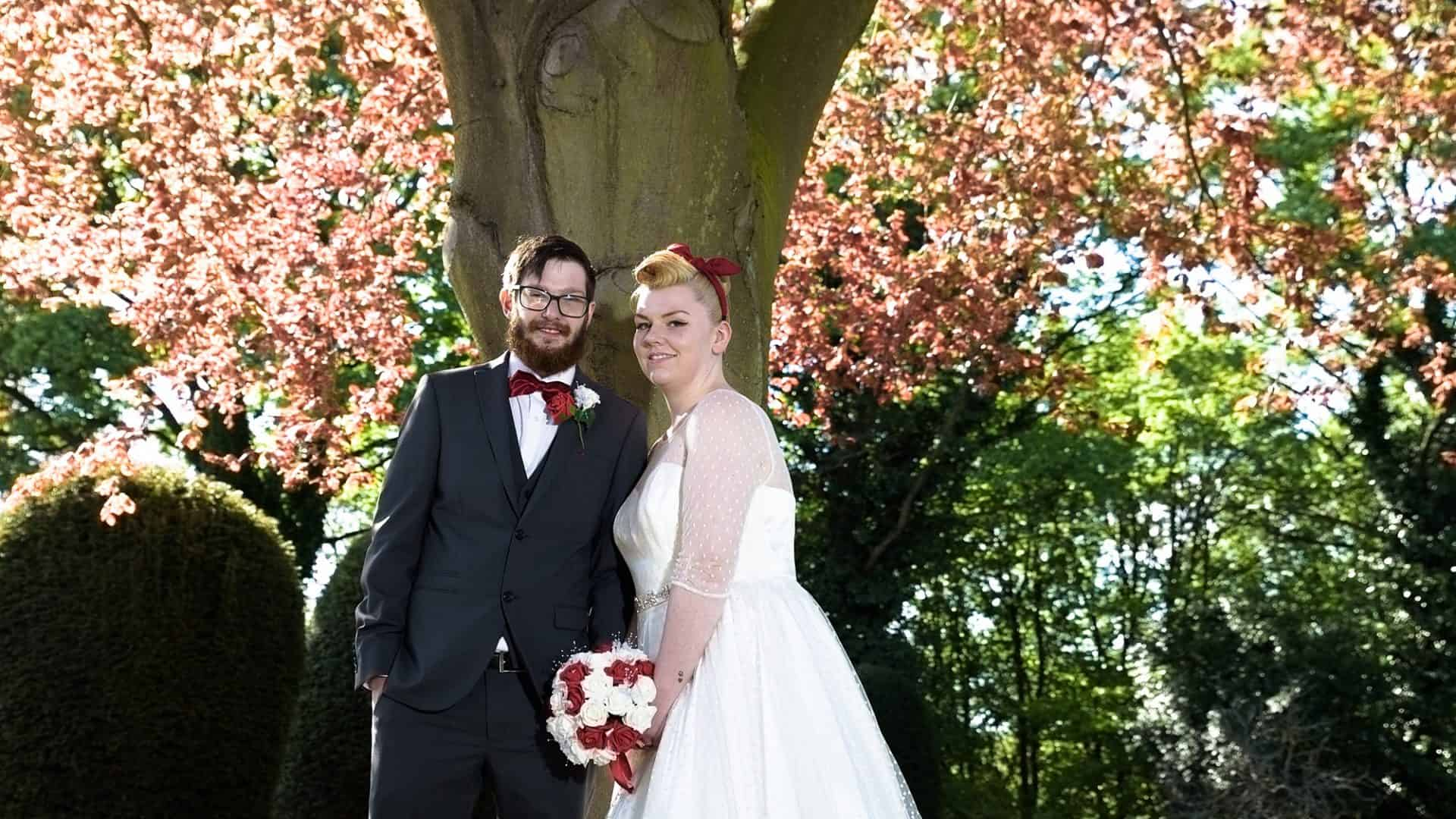 Bride and groom under the shade of a tree