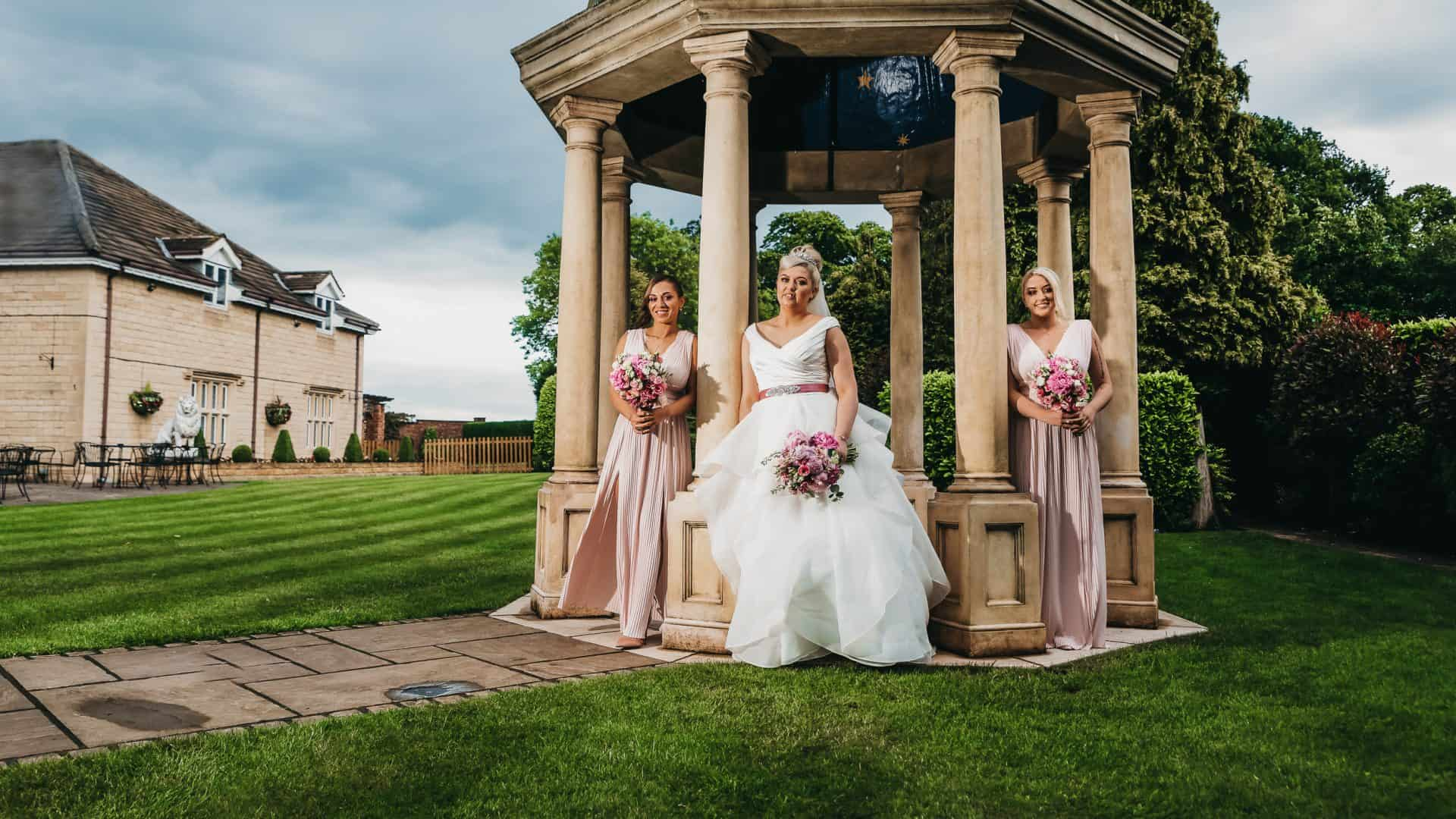 Bride with her two brides maids posing for a picture under the gazebo at rogerthorpe manor