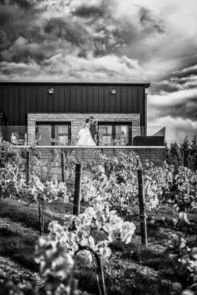 Epic feature black and white images of bride and groom on the balacany at the holmfirth vineyard