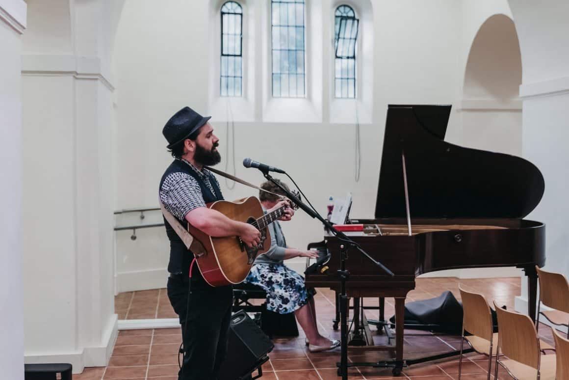 This image show a wedding entertainer singing and playing guitar at a wedding
