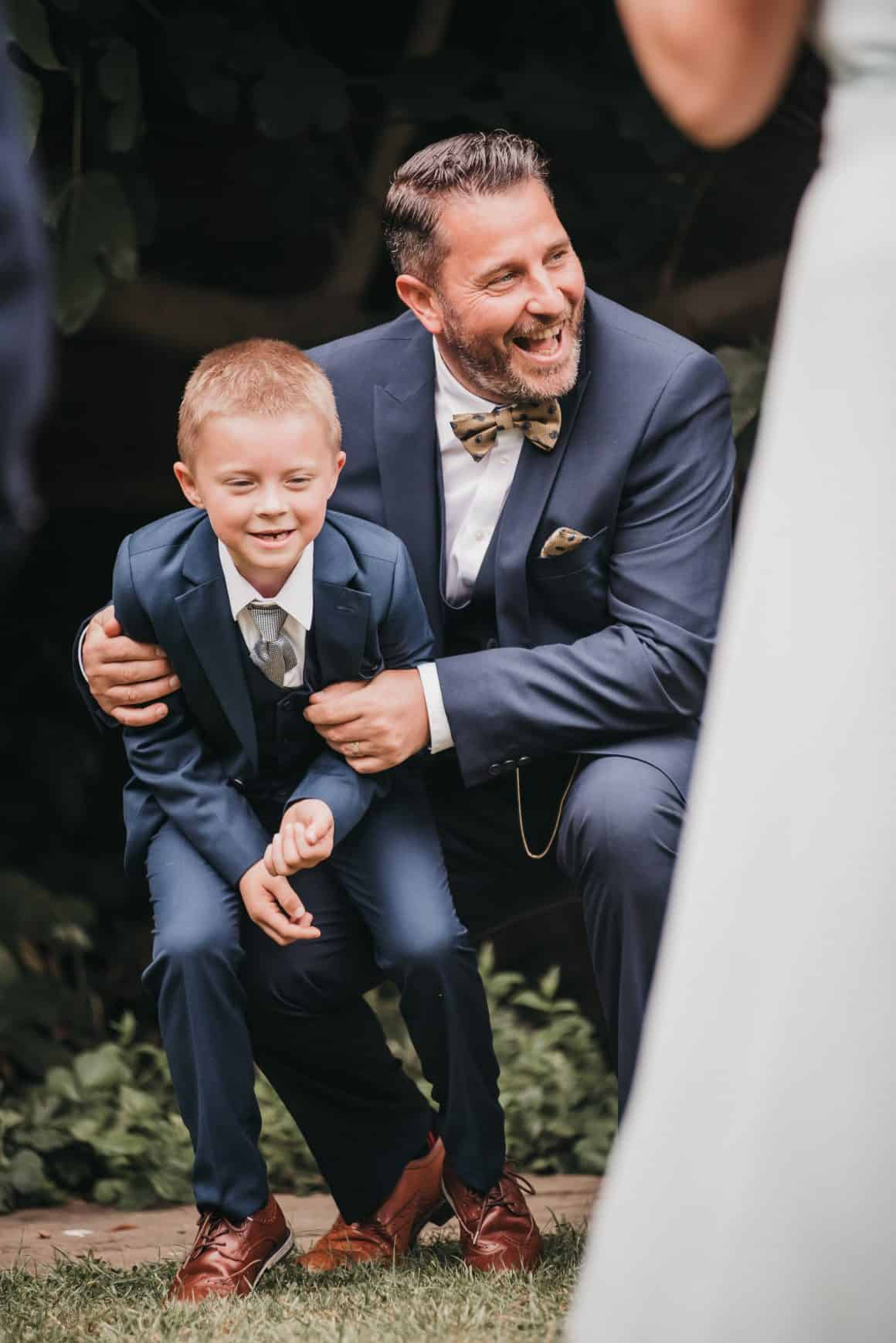 this image shows a little boy having fun with his dad at a wedding