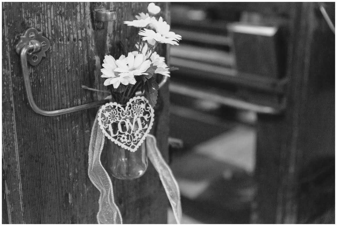 Love Sign and Flowers attached to a church pew