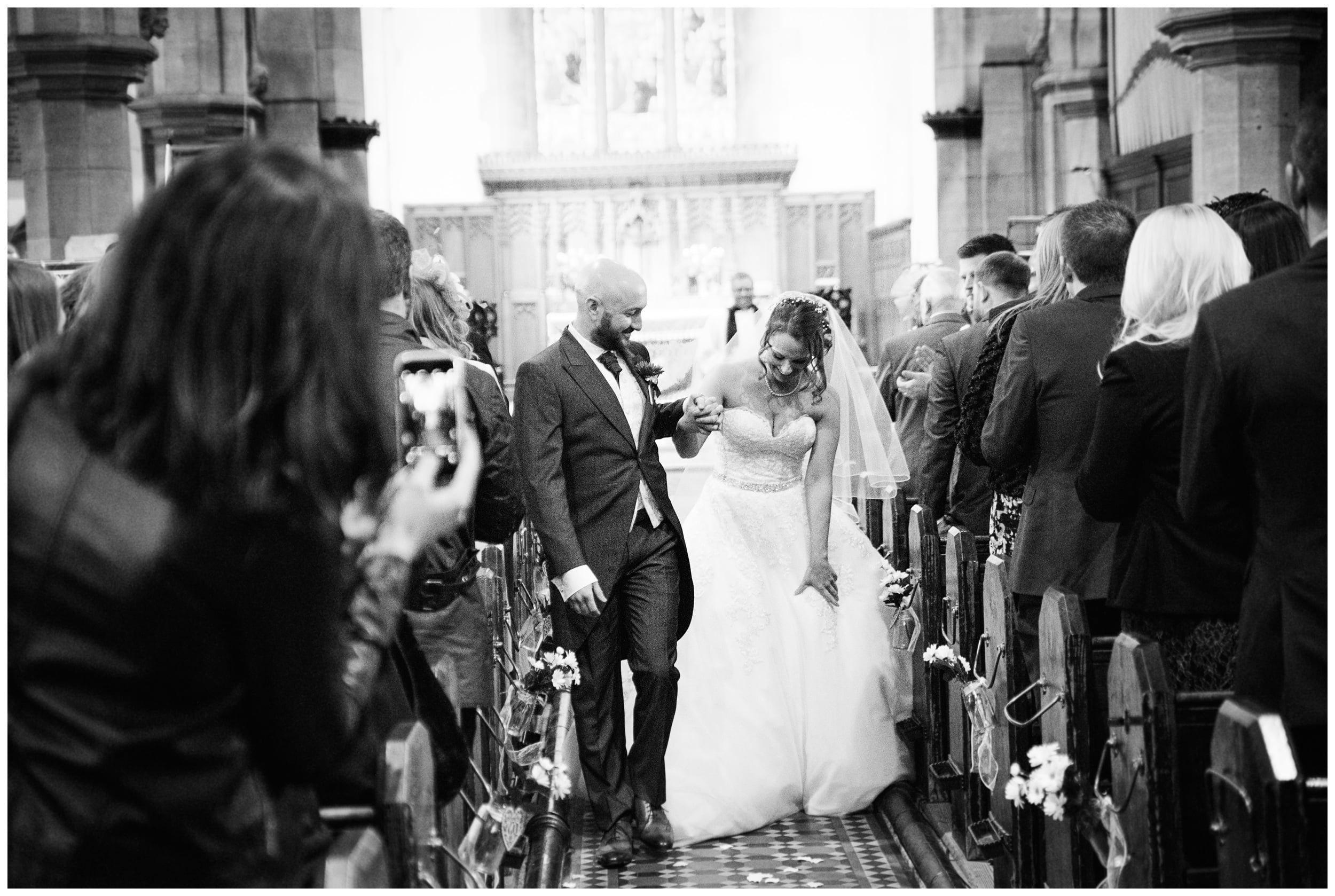 Stunning black and white picture of Bride and groom walking down the church aisle while guest cheer