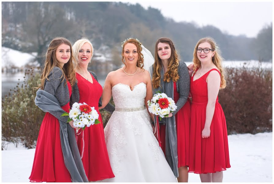 Bride with bridesmaids outside at Waterton Hall Wakefield, on a snowy winters day with the lake in the background