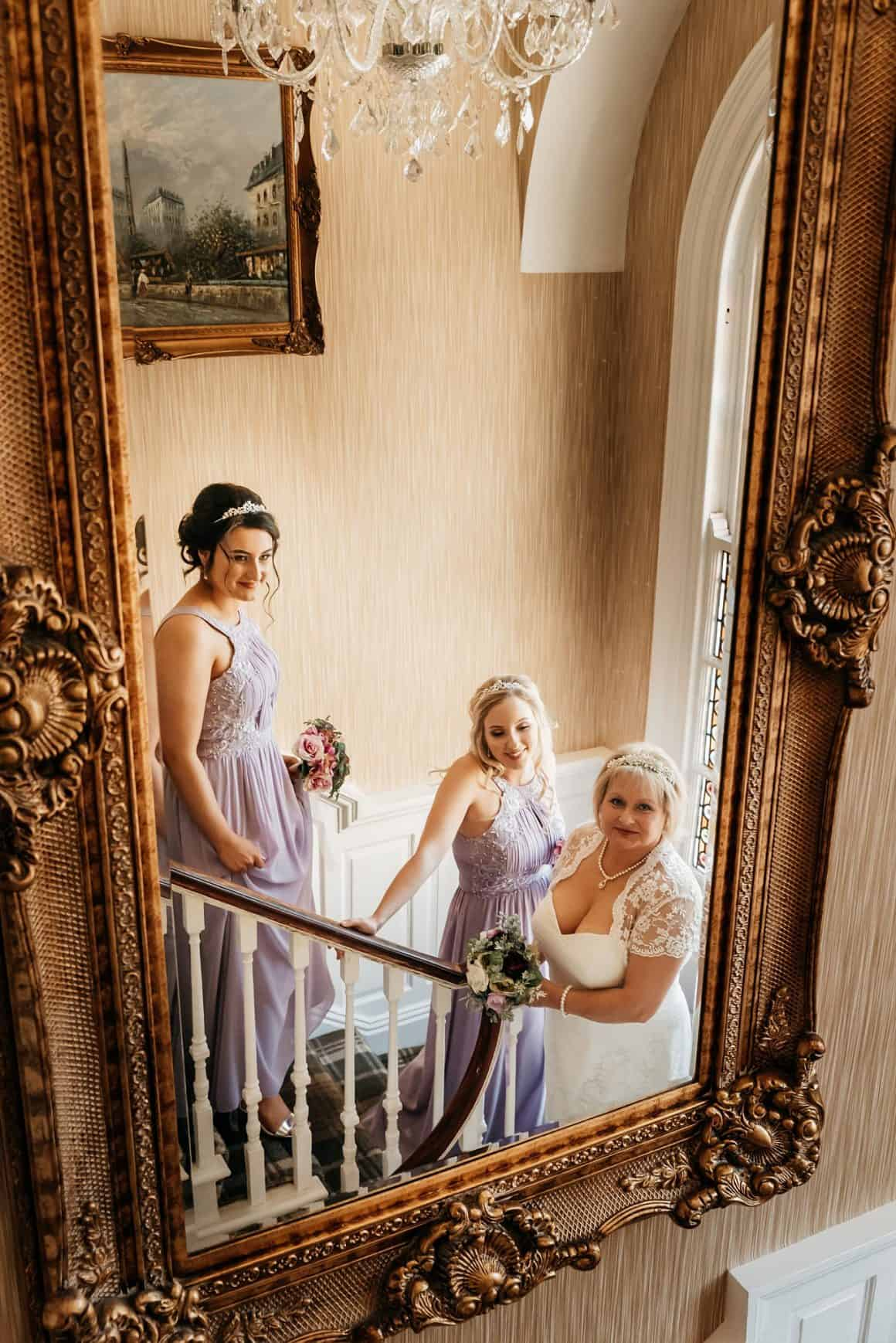 This image shows a bride and two bridesmaids looking into the mirror at the wedding venue king Croft Hotel, Pontefract