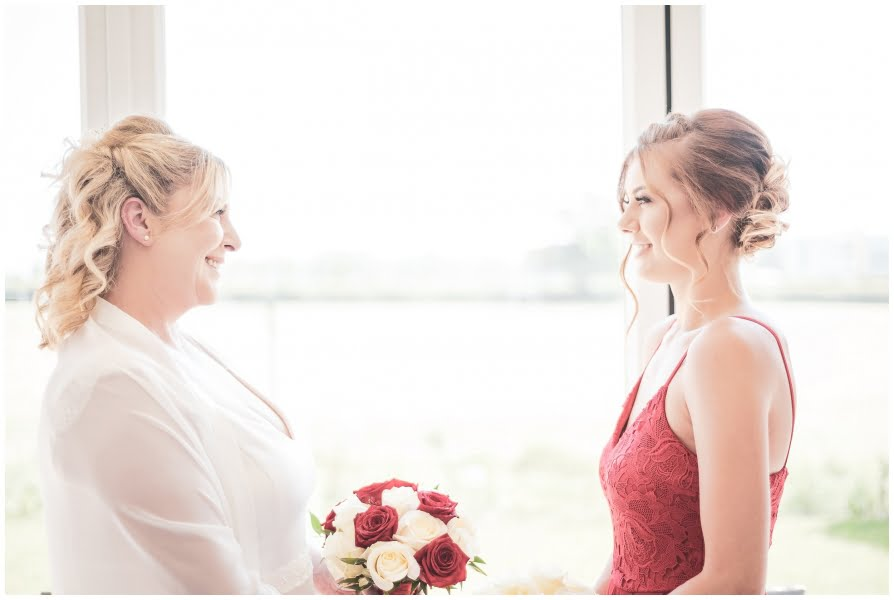 Side view of bride holding flowers, smiling at bridesmaid ,backlit with beautiful window sunlight