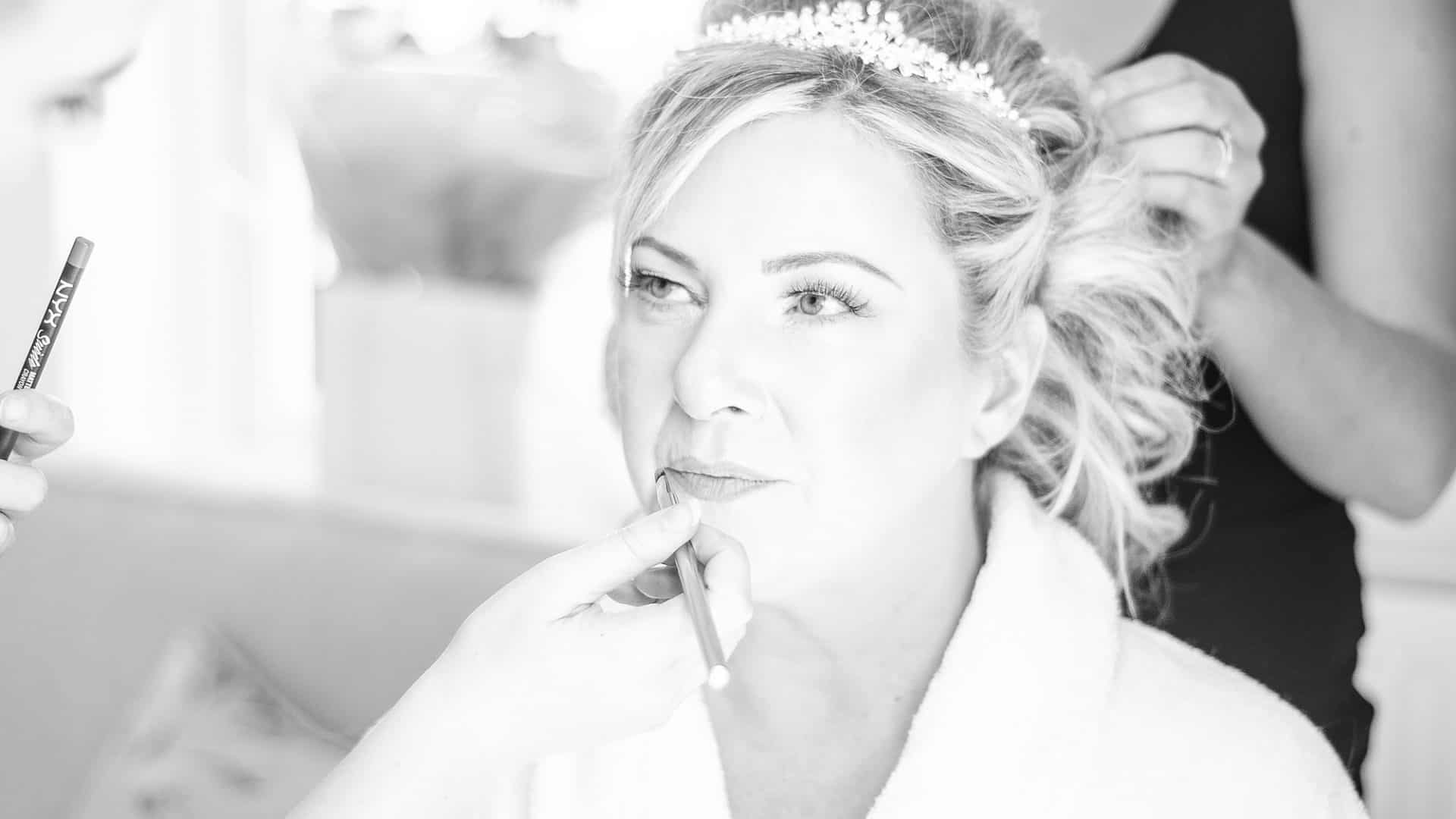 black and white images of bride getting her makeup put on