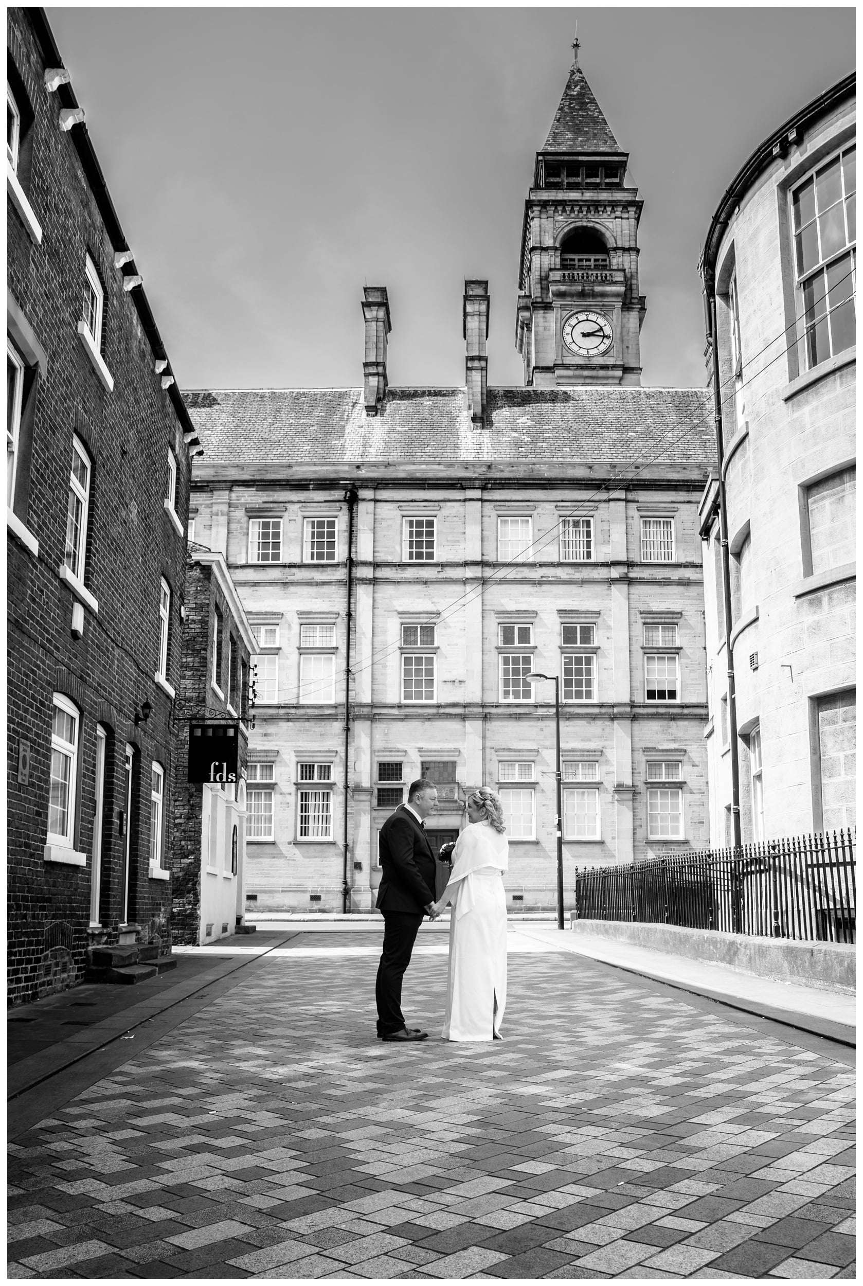 Bride and Groom Standing in Wakefield City Street behind TownHall