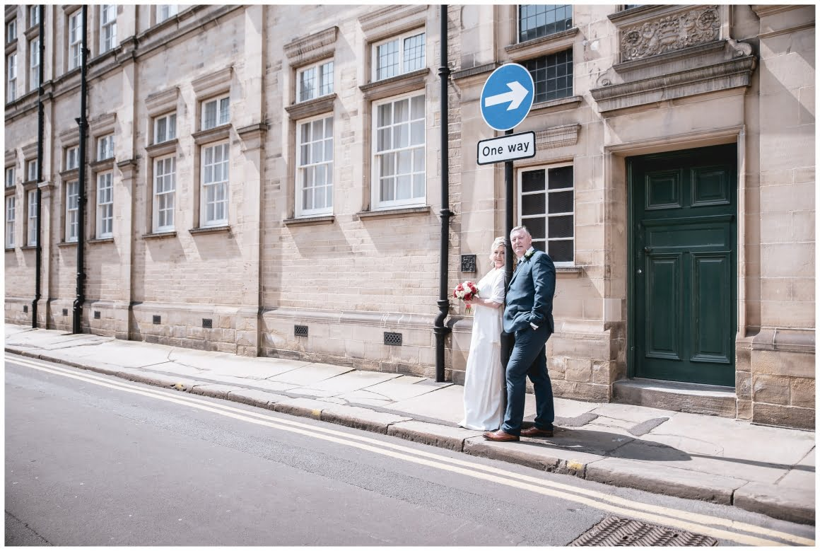 Bride and Groom pose, one way street at the side of wakefield town hall