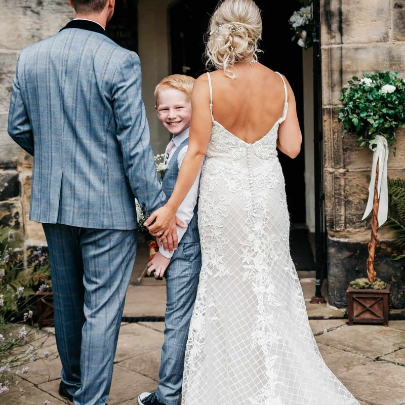 this image shows a page boy peaking at the camera behind the bride and groom