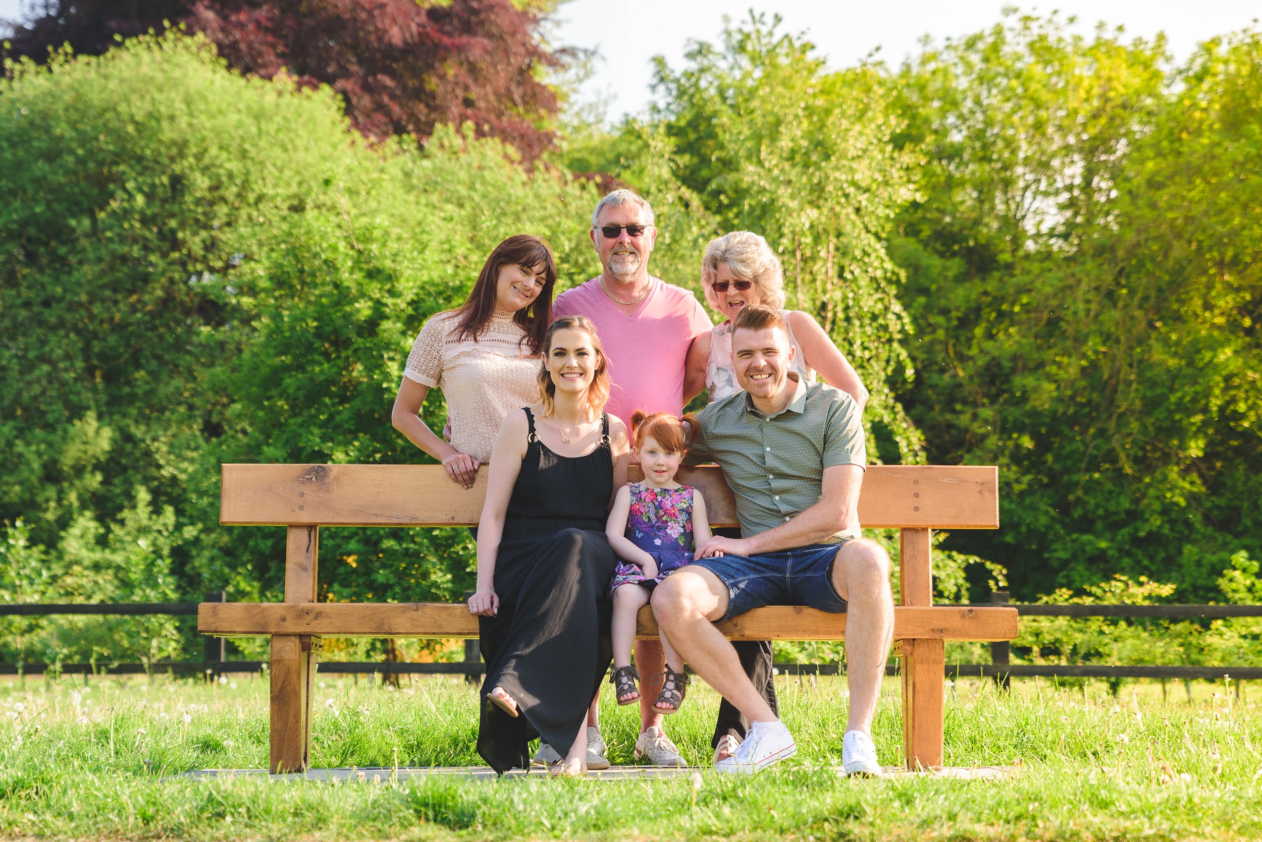 Portrait of a family sat on a bench , in the countyside