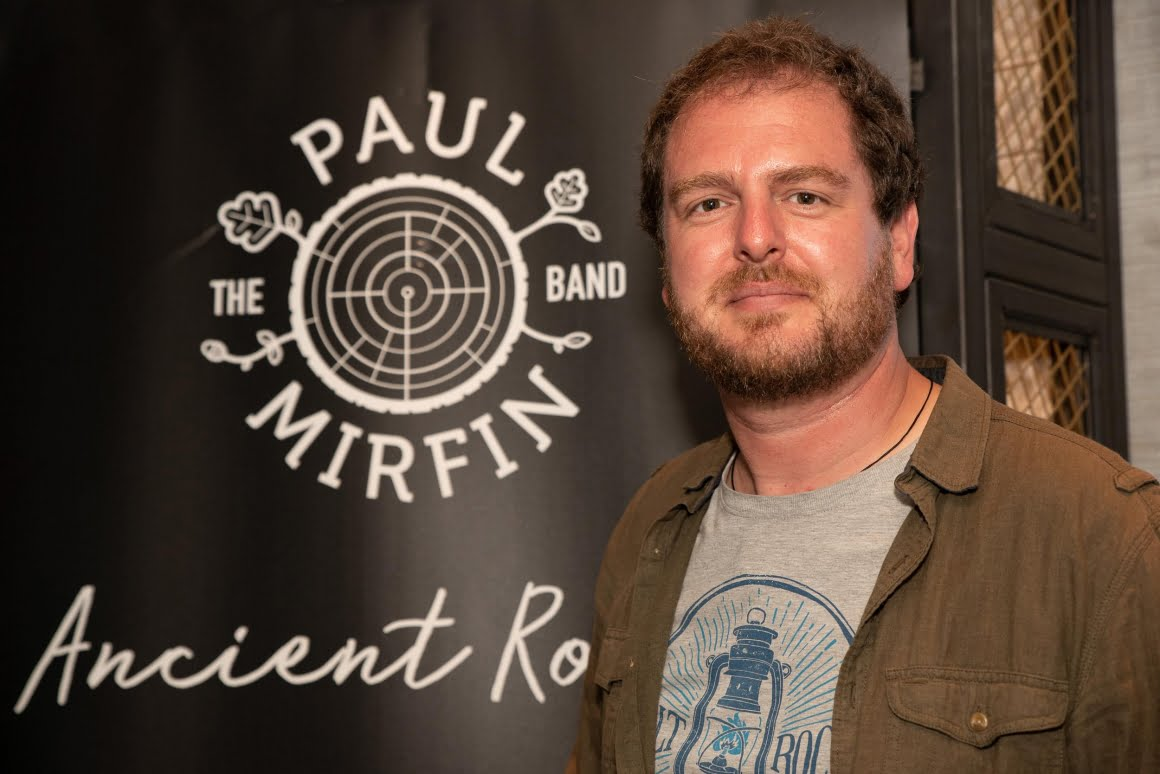 Picture of Paul Stood next to a poster with the album artwork on and band logo