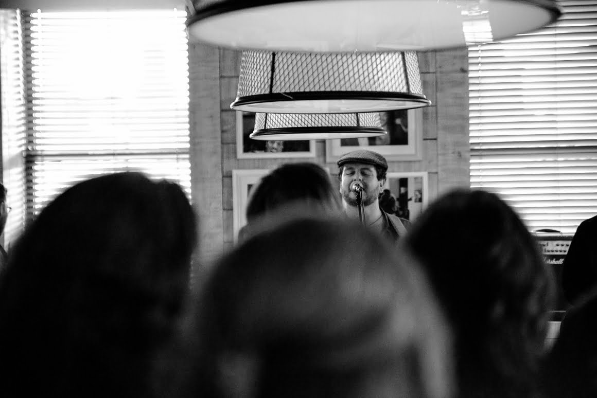 black and white of paul singing, shot from back of the room