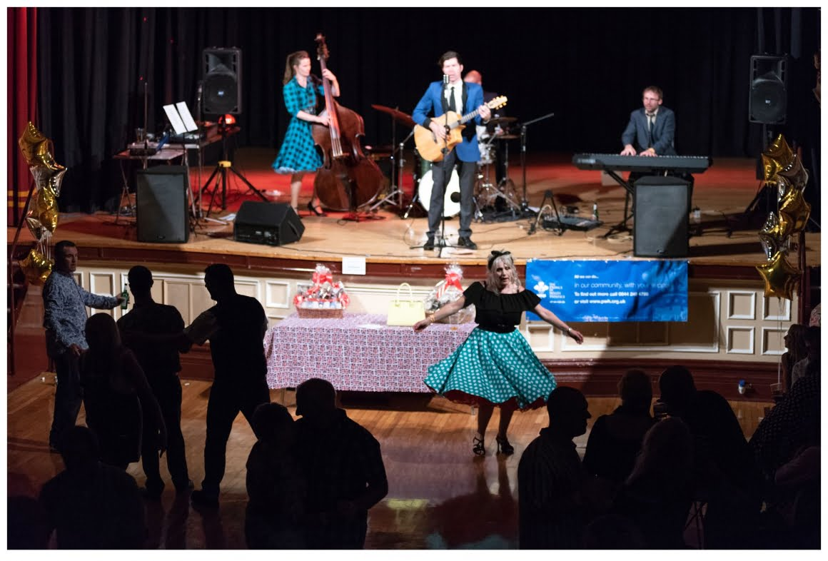 the milkshakers playing on stage at pontefract town hall with people dancing in the audience
