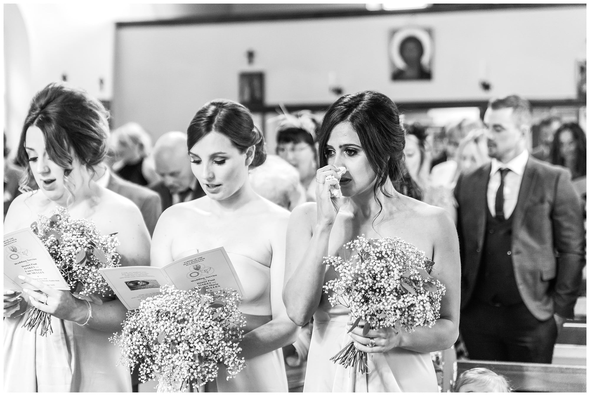 Bridesmaid wiping tear away the Holy Family Church Slaithwaite
