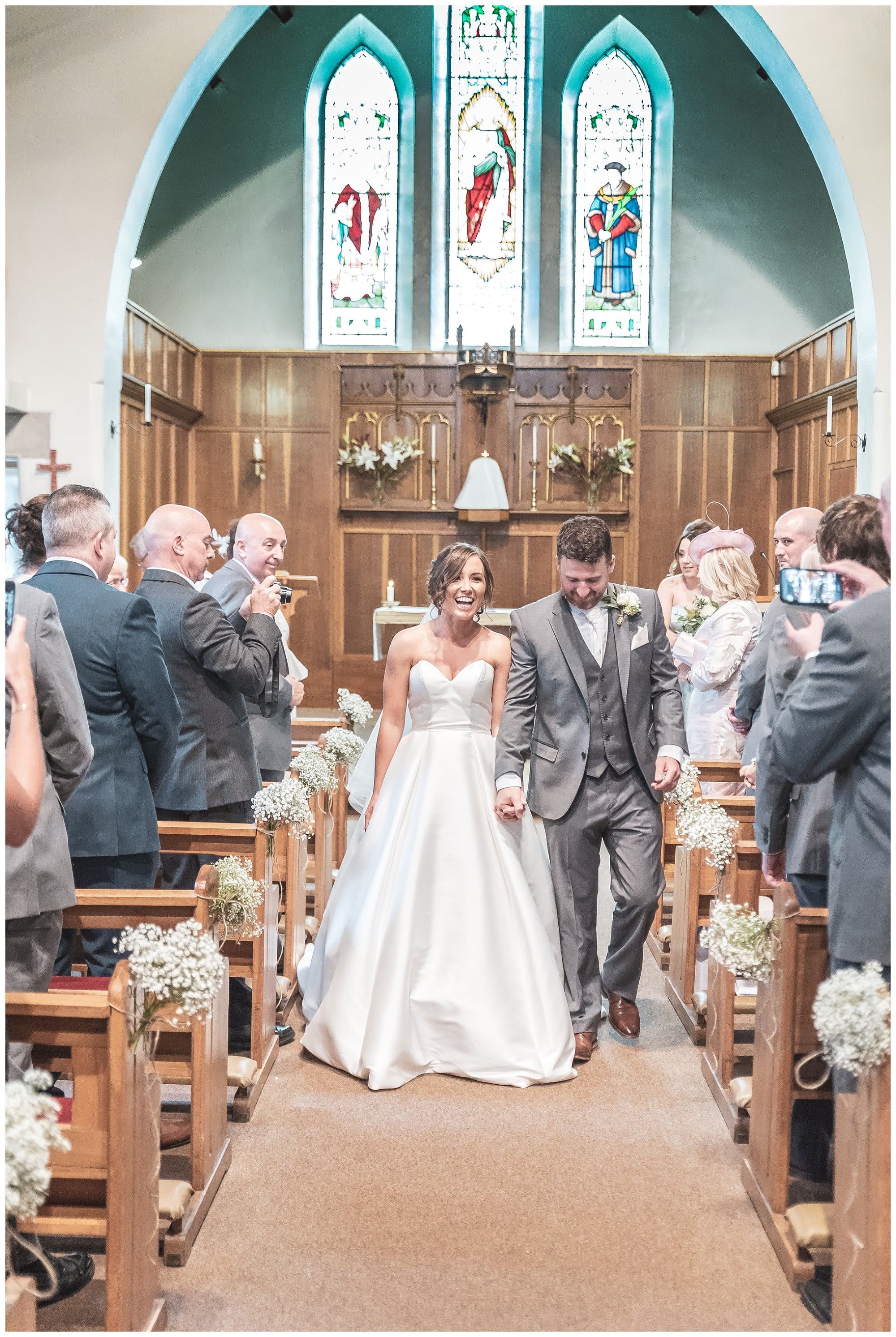 Bride and groom smiling walking down the church aisle after just getting married at the Holy Family Church Slaithwaite