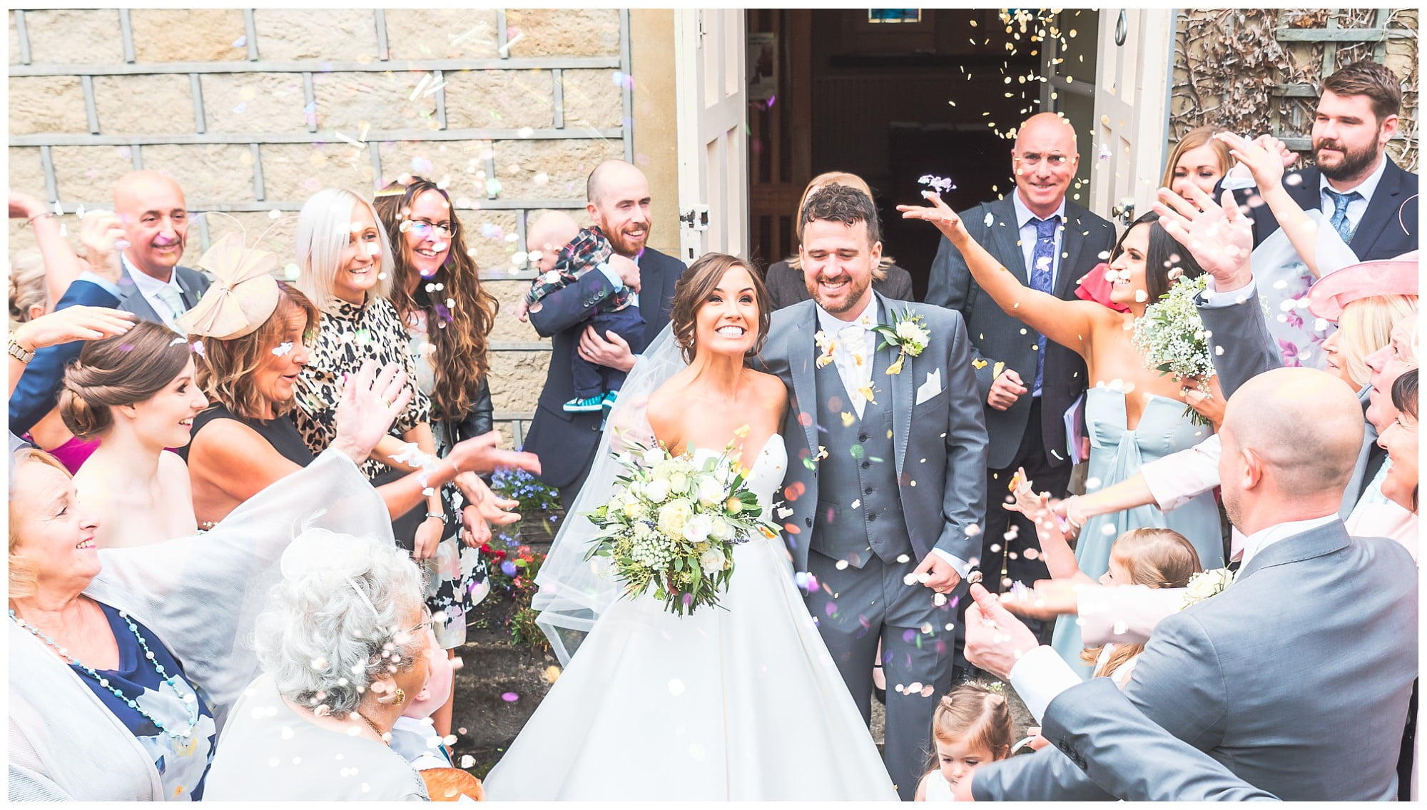 bride and groom exit church with confetti in the air Holy Family Church Slaithwaite