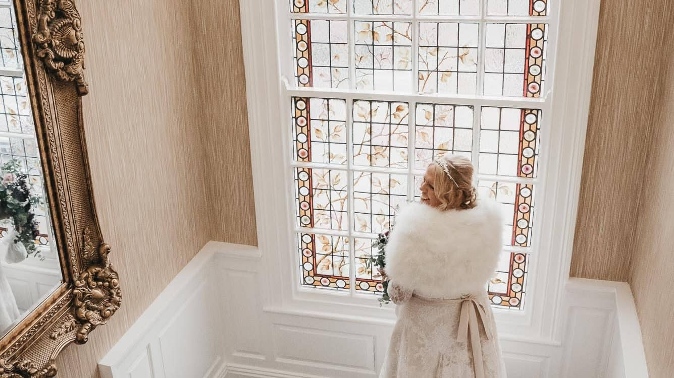 bride walking down the steps next to stained glass window - kings croft hotel
