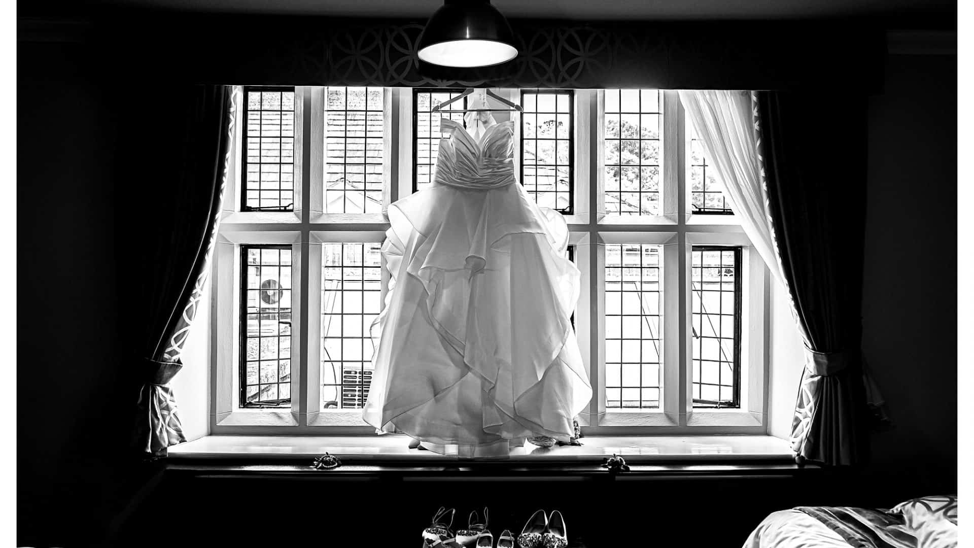 Wedding Dress hung up in front of window at rogerthorpe manor