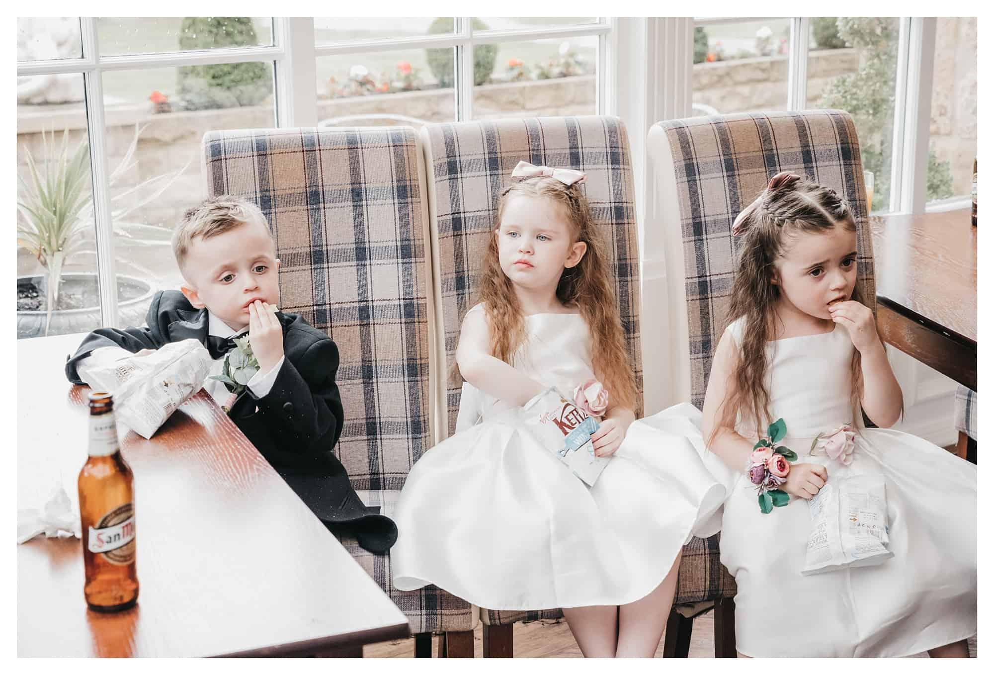 this image show 3 young children having a quick snack break eating crisp at a wedding