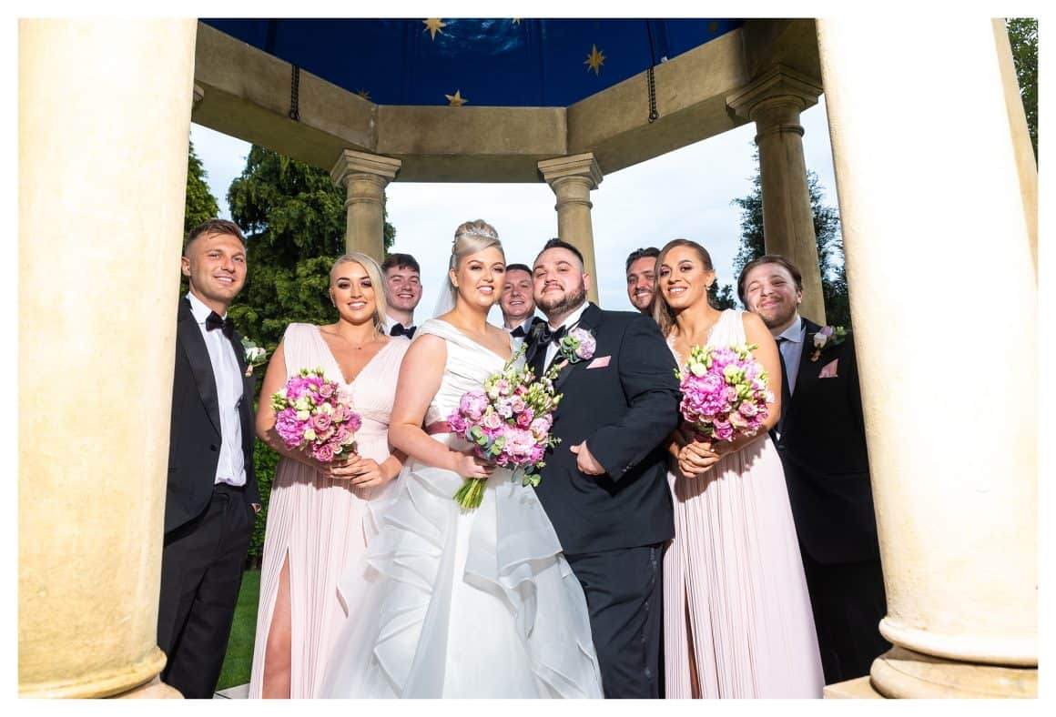 In this image, Both the Bridesmaid and the Groomsmen including the bride and groom are looking down at the photographer, taken at Rogerthorpe Manor, West Yorkshire
