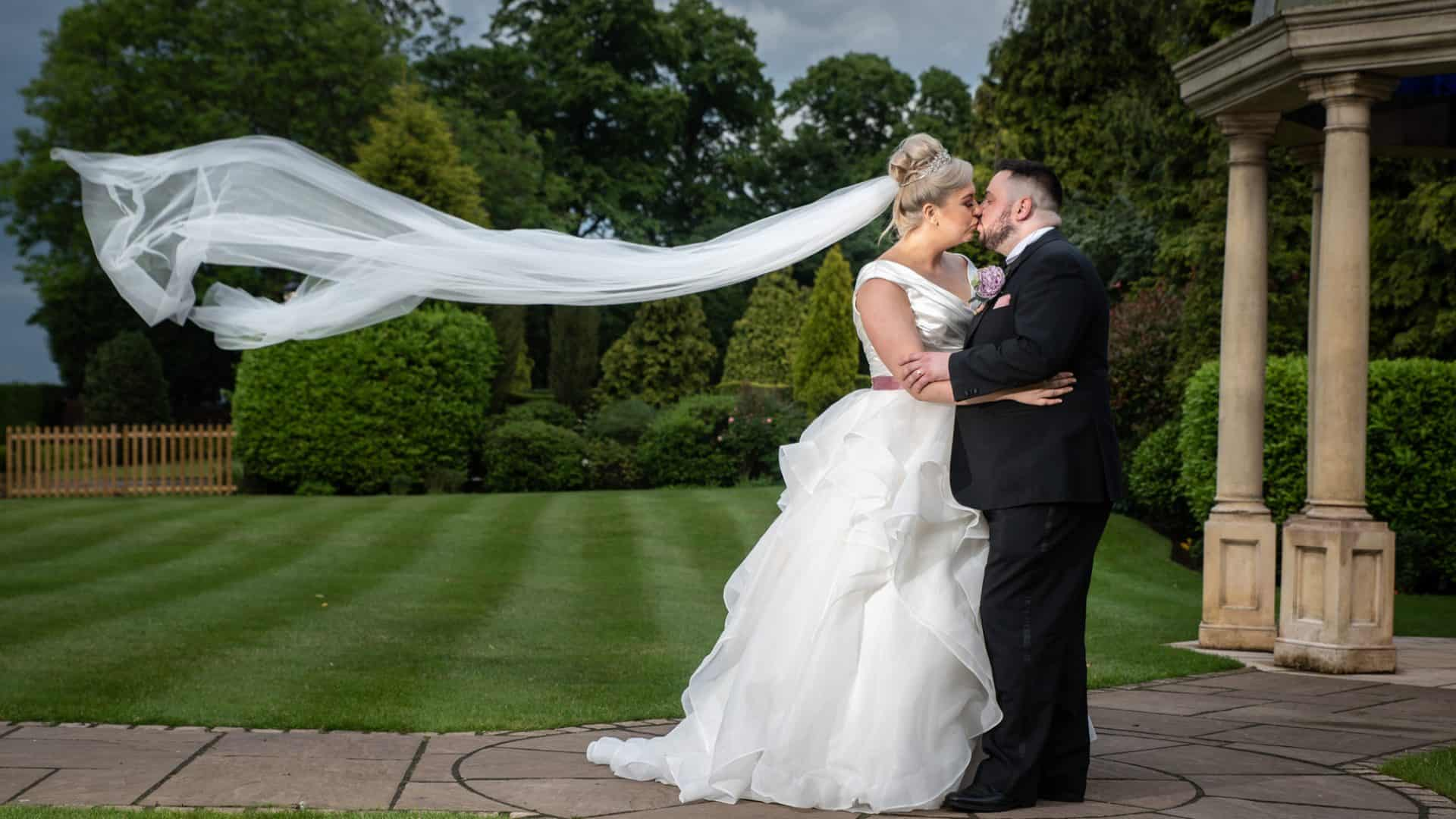 Bride and groom kissing with her vale blowing in the wind at rogerthorpe manor