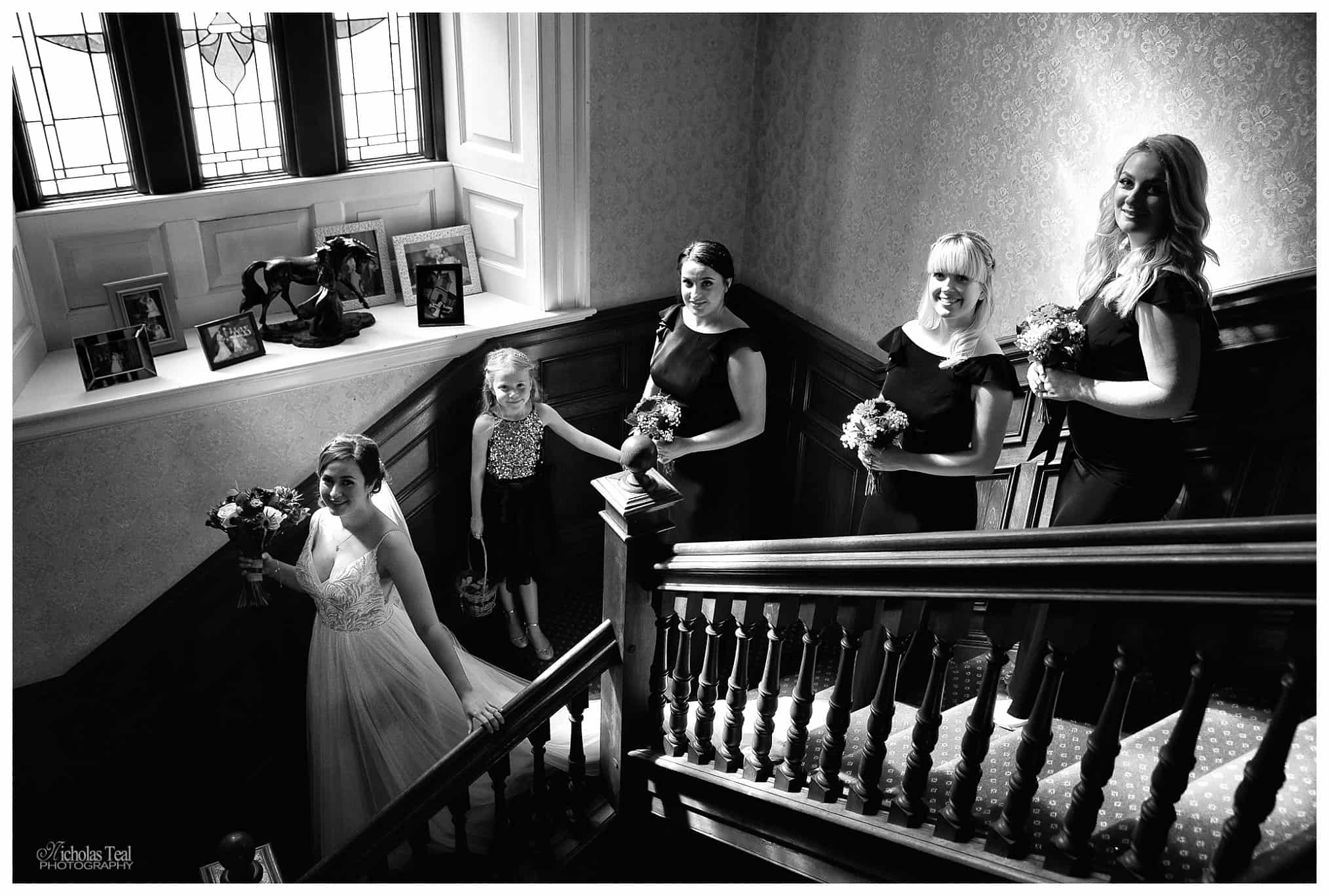bride and bridal party walking down famous staircase at Bagden Hall