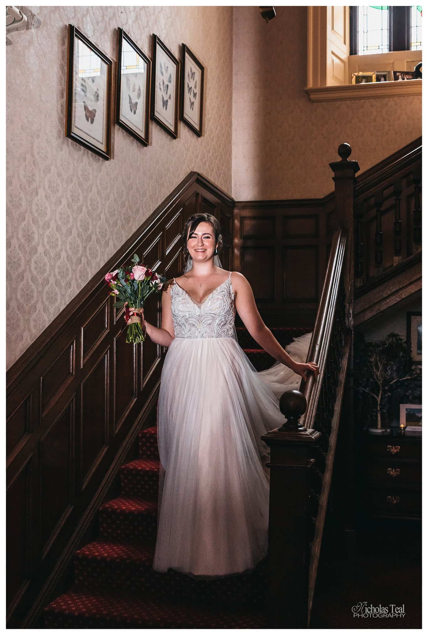 bride walking down the famous staircase at Bagden Hall with flowers in her hand