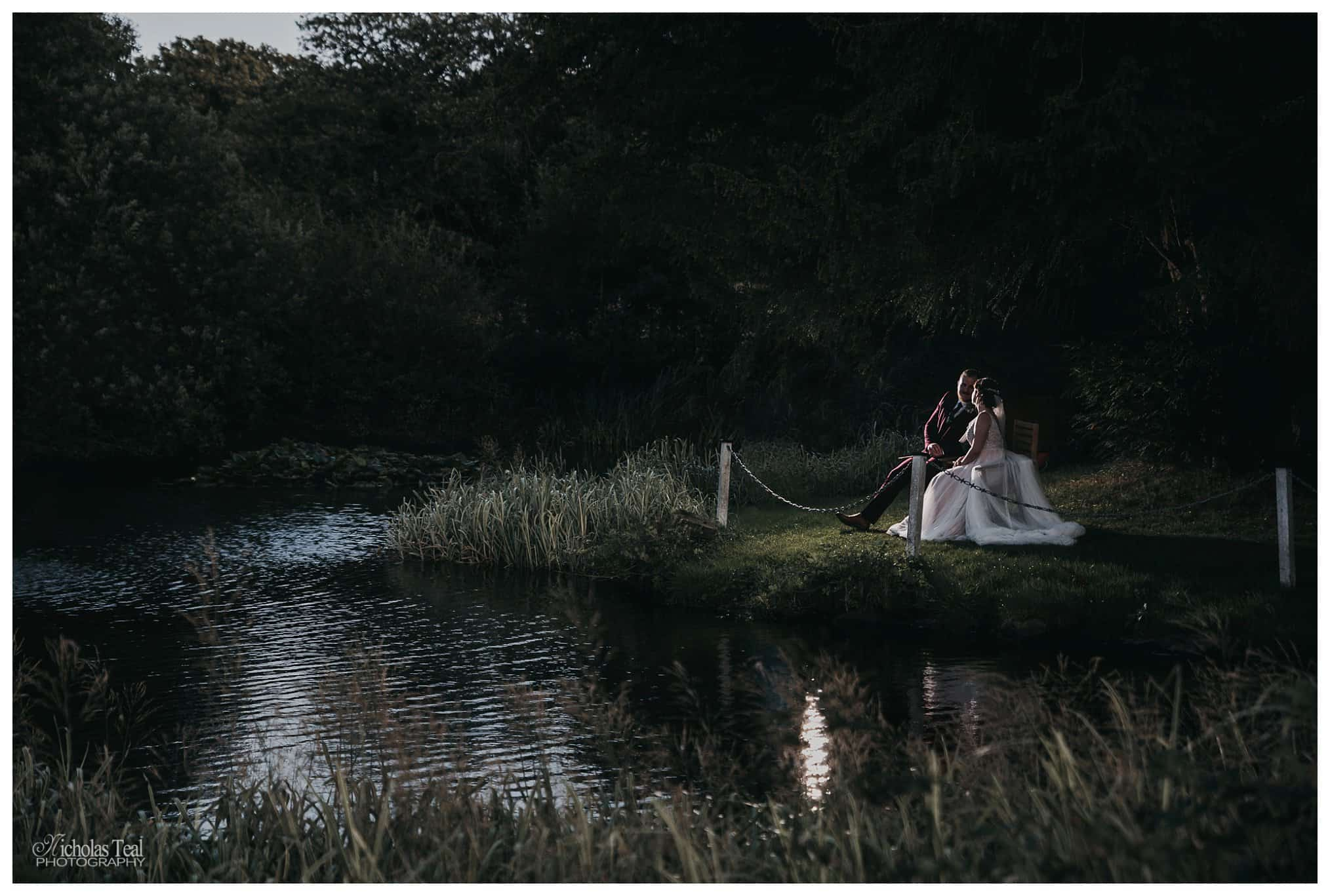 stunning flash light image of bride and groom sat on a bench next to pond enjoying a moment at Bagden Hall