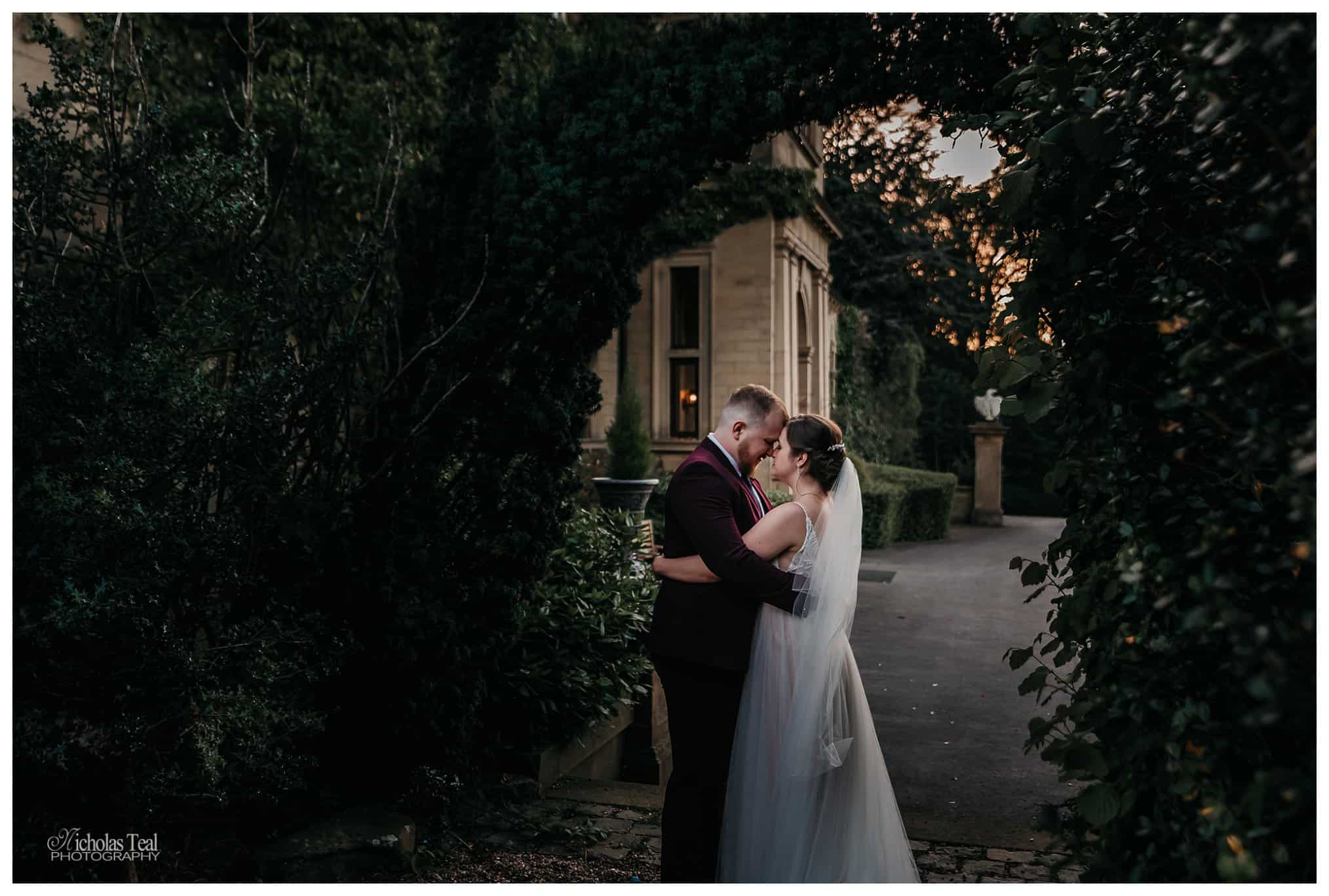 beutifull posed image of bride and groom kissing under a arch with Bagden Hall visible behind them - Bagden Hall