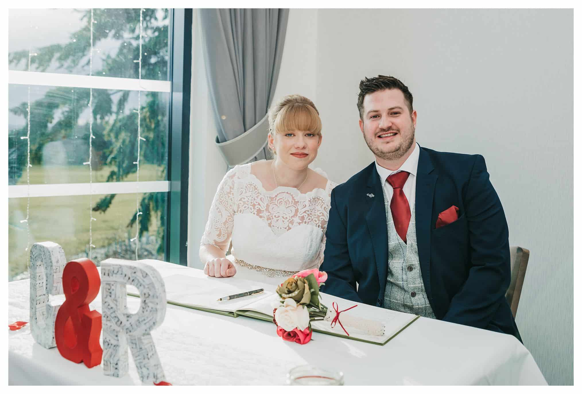 Bride and Groom sitting at the table after just singing the register
