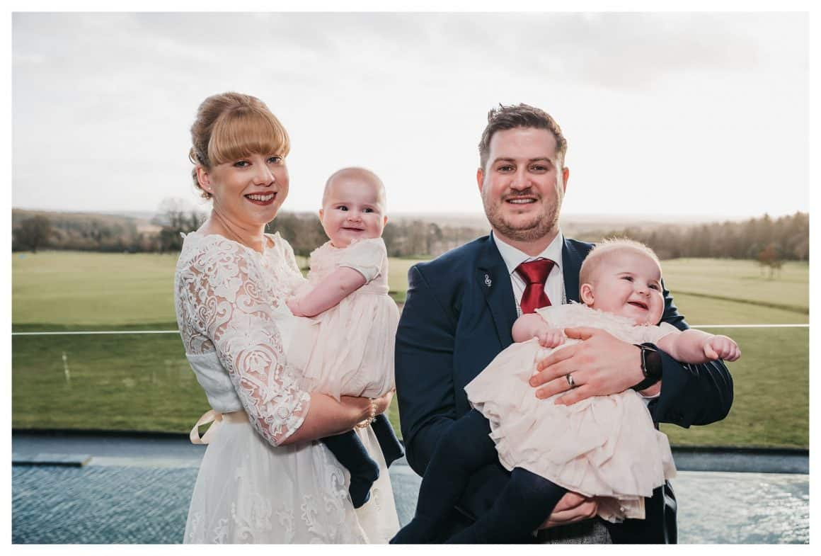 this image shows a bride and groom holding two baby twin girls who are both smiling and laughing
