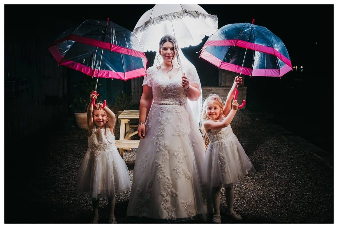 Creative light image using flash, with the bride holding a umbrella with her two flower girls who are also holding up umbrellas