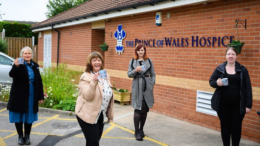 Official promotion images of the ladies holding the mugs , outside of the hospice