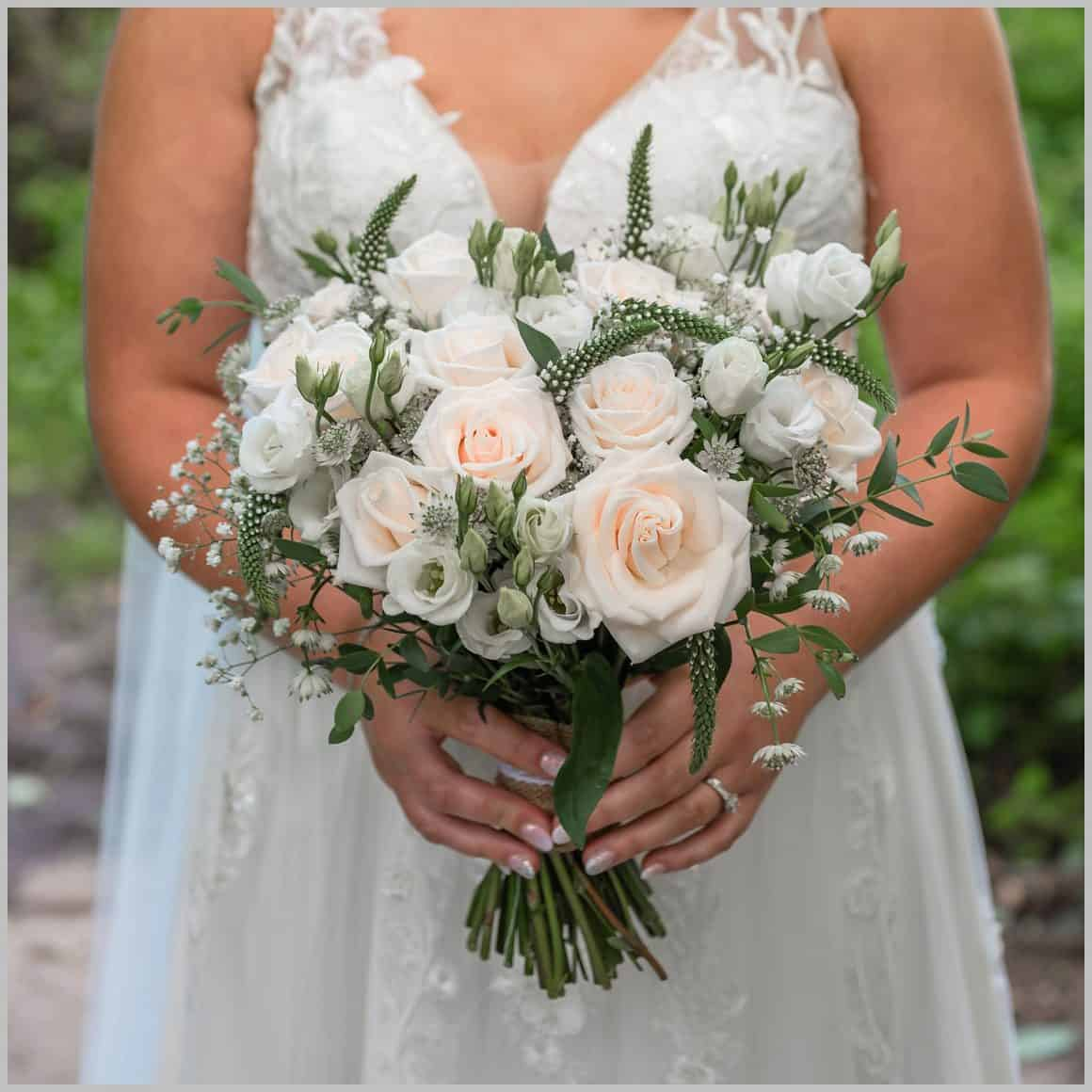 Flower detail shot showing white roses in brides hands