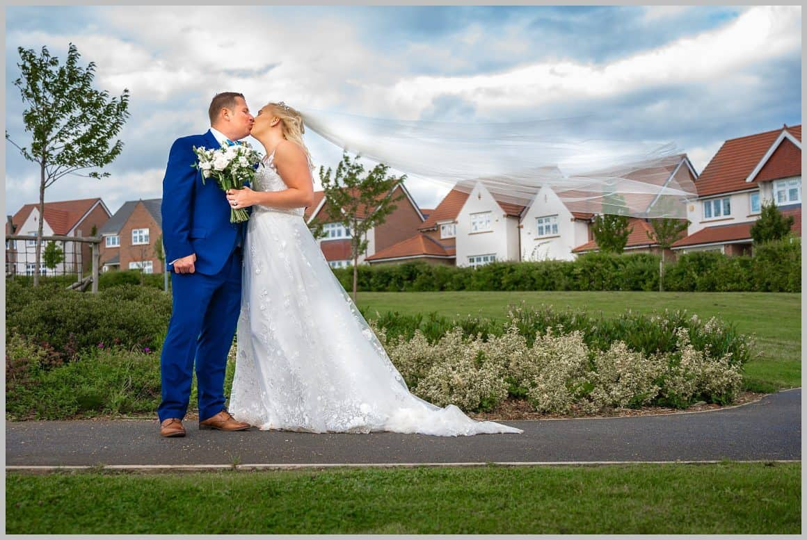 Hero shot of bride and groom kissing in the street with the brides vale blowing in the wind.