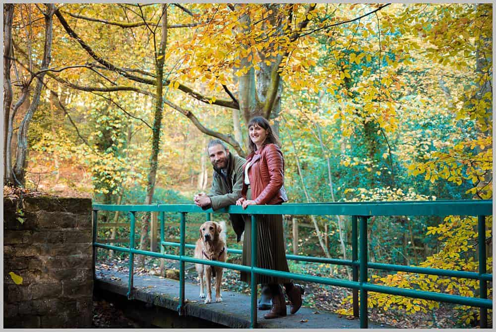 This picture shows  a couple posing on the  green metal bridge  at The Rivelin Valley sheffield