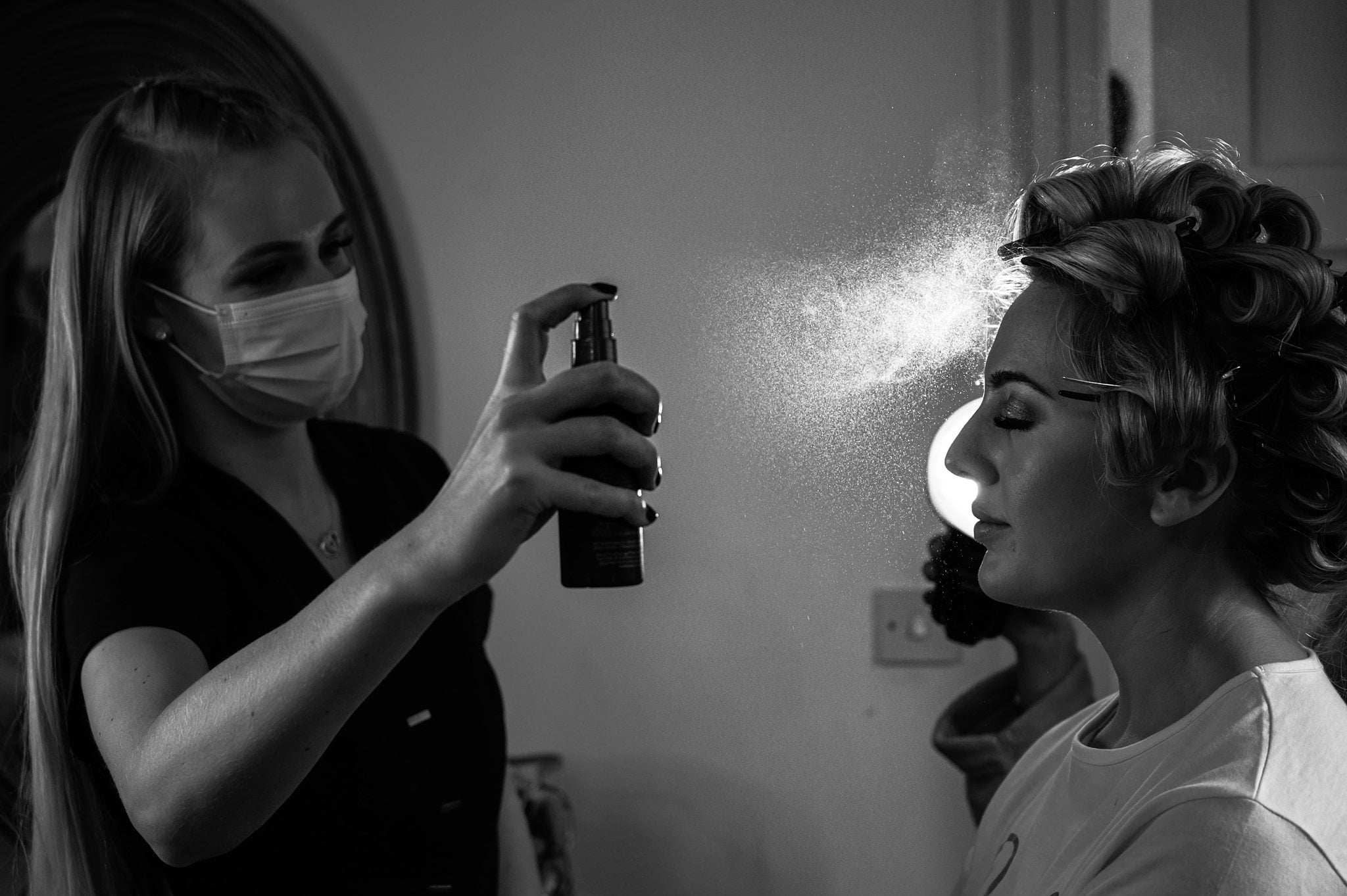 This image shows a flash photography image of a bride getting her hair sprayed light from behind
