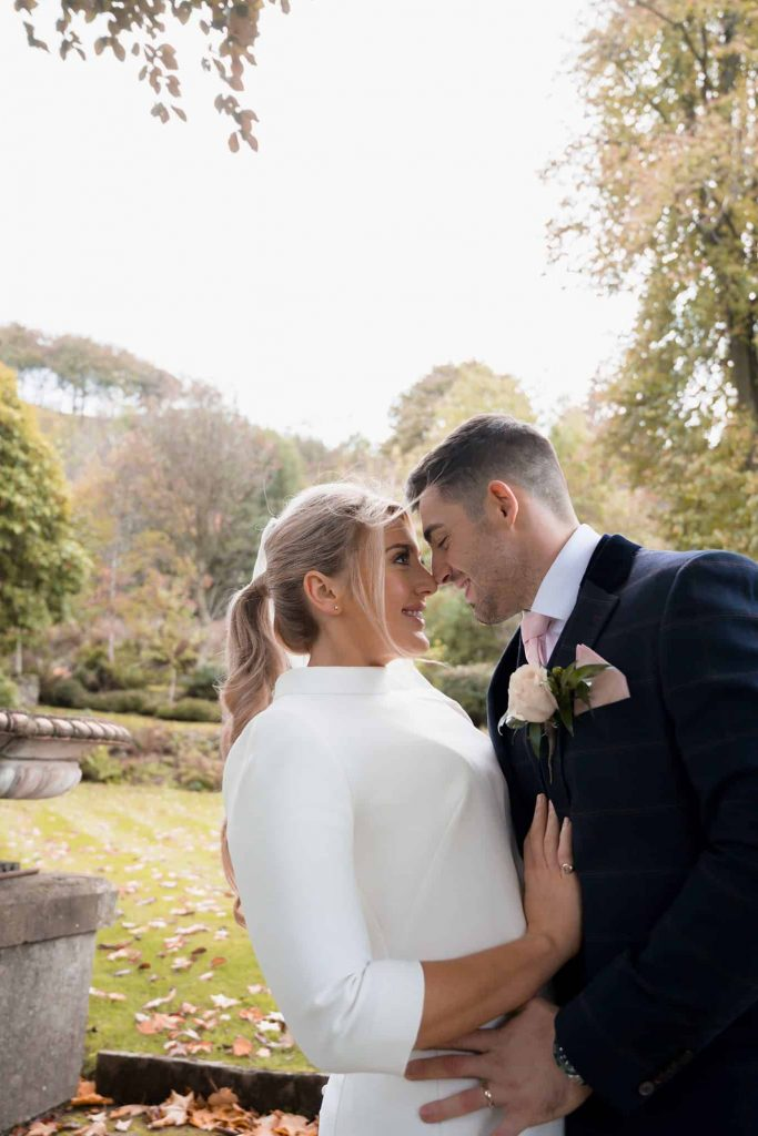 This image shows a bride and groom embracing each other with the groom holding the bride round the hips in a posed picture, location is outside in a beautiful garden in Halifax