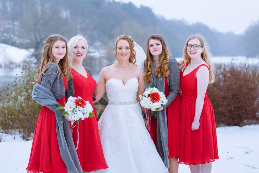 This image shows a bride with her 4 bridesmaids posing for a shot in the snow