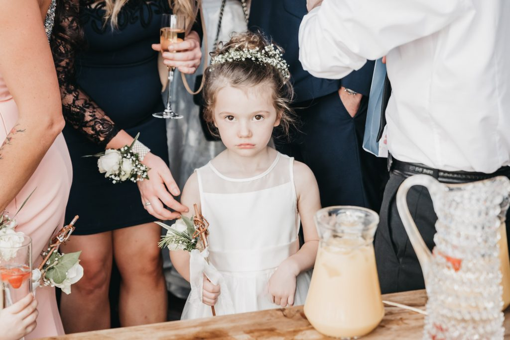 This image is of a little flower girl at a wedding looking directly into the camera, the expression on her face is one of been not happy