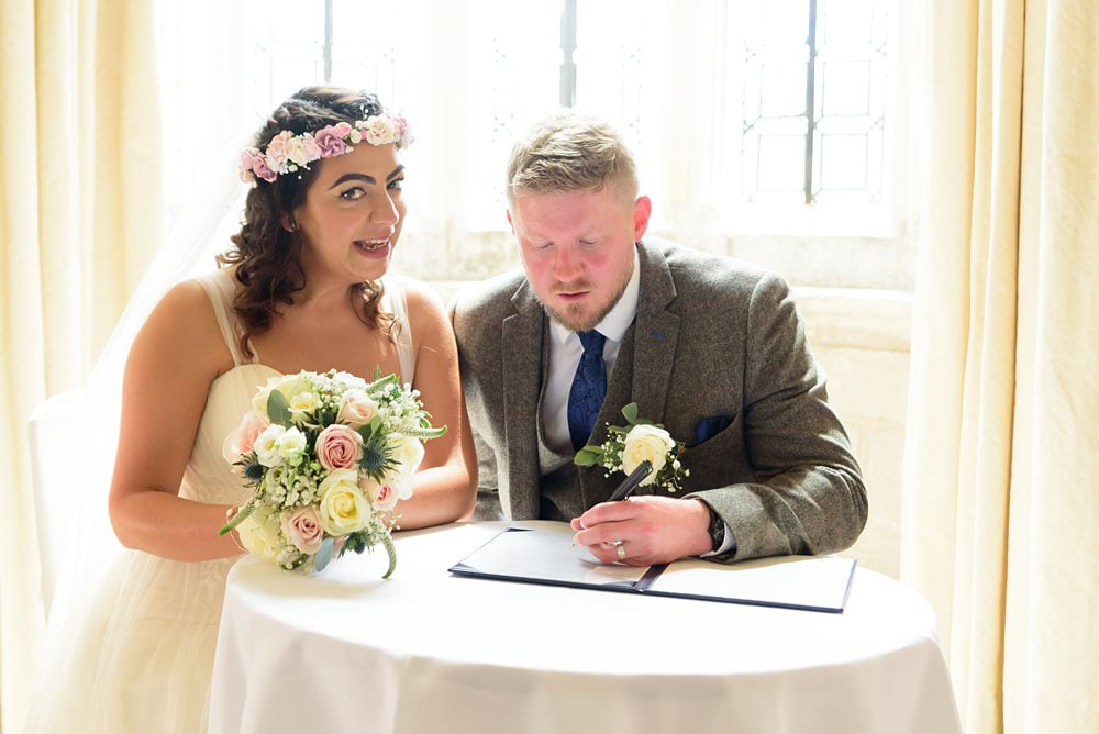 Bride and Groom signing register photograph Fountains Hall Rippon, Fountains Hall Rippon Photos, Fountains Hall Wedding photographer